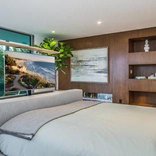 Пример оригинального дизайна: хозяйская спальня среднего размера в современном стиле с коричневыми стенами, полом из керамической плитки, горизонтальным камином, фасадом камина из дерева и серым полом