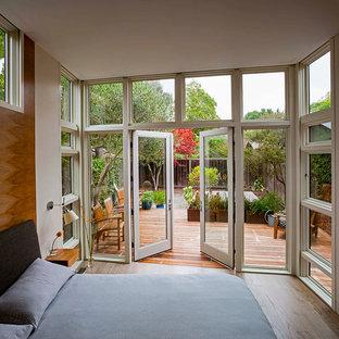 Foto de dormitorio principal, minimalista, de tamaño medio, sin chimenea, con paredes blancas y suelo de madera en tonos medios