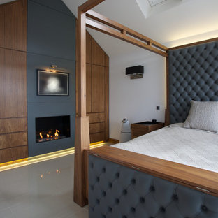 Inspiration for a contemporary master bedroom in London with white walls and a standard fireplace.
