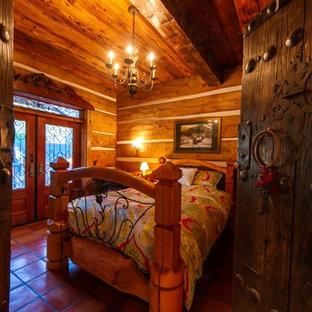 Diseño de dormitorio principal, de estilo americano, de tamaño medio, con paredes marrones, suelo de baldosas de cerámica y suelo naranja
