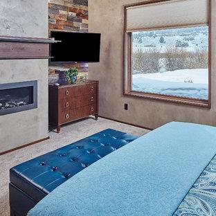 Imagen de dormitorio principal, actual, de tamaño medio, con paredes beige, moqueta, marco de chimenea de yeso y chimenea tradicional