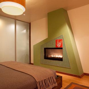Ejemplo de dormitorio principal, minimalista, grande, con paredes blancas, suelo de bambú, chimenea tradicional y marco de chimenea de baldosas y/o azulejos