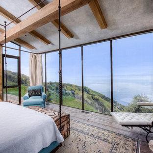 Стильный дизайн: огромная хозяйская спальня в средиземноморском стиле с серыми стенами, паркетным полом среднего тона, стандартным камином и фасадом камина из бетона - последний тренд