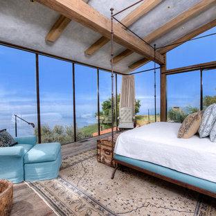 Idee per un'ampia camera matrimoniale mediterranea con pareti grigie e pavimento in legno massello medio