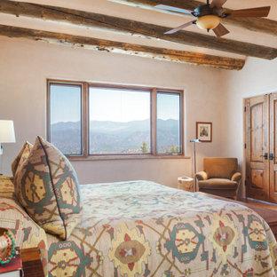 アルバカーキの大きいサンタフェスタイルのおしゃれな主寝室 (白い壁、無垢フローリング、暖炉なし、茶色い床) のインテリア