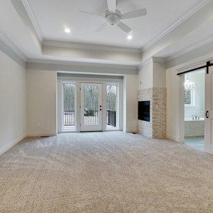 Diseño de dormitorio principal, clásico, grande, con paredes beige, moqueta, chimenea de esquina, marco de chimenea de ladrillo y suelo beige