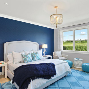 Inspiration for a large coastal master bedroom in New York with blue walls and light hardwood flooring.