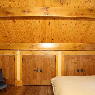 Foto de dormitorio tipo loft, de estilo americano, grande, con paredes amarillas y suelo de madera en tonos medios