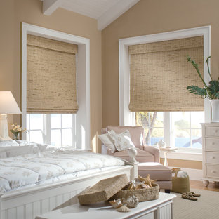 Example of a large coastal guest light wood floor bedroom design in Indianapolis with beige walls