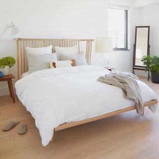 Imagen de dormitorio principal, escandinavo, pequeño, con paredes blancas, suelo de madera clara, chimenea de doble cara, marco de chimenea de piedra y suelo beige