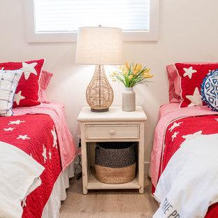 Idées déco pour une grande chambre d'amis bord de mer avec un mur blanc, un sol en bois clair, aucune cheminée et un sol beige.