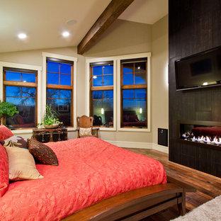 Foto di una camera da letto american style con pareti beige, pavimento in legno massello medio, camino lineare Ribbon e cornice del camino piastrellata
