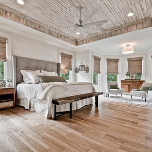 Photo of a large arts and crafts master bedroom in Other with white walls, light hardwood floors and brown floor.