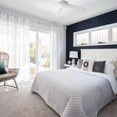 Example of a mid-sized beach style guest carpeted bedroom design in Brisbane with blue walls