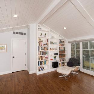 Modelo de dormitorio principal y machihembrado, de estilo de casa de campo, de tamaño medio, con paredes blancas, suelo de madera en tonos medios y suelo marrón