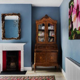 Idee per una camera degli ospiti boho chic di medie dimensioni con pareti blu, parquet chiaro, camino classico e cornice del camino in legno