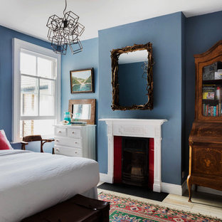 Design ideas for a mid-sized traditional guest bedroom in London with blue walls, light hardwood floors, a standard fireplace and a wood fireplace surround.