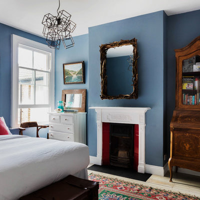 Mid-sized elegant guest light wood floor bedroom photo in London with blue walls, a standard fireplace and a wood fireplace surround