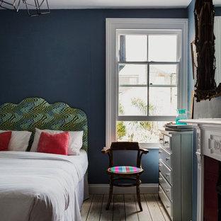 ロンドンの中サイズのエクレクティックスタイルのおしゃれな客用寝室 (青い壁、淡色無垢フローリング、標準型暖炉、木材の暖炉まわり)