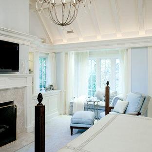 На фото: хозяйская спальня среднего размера в классическом стиле с синими стенами, ковровым покрытием, стандартным камином, фасадом камина из камня и бежевым полом с