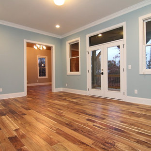 Example of a huge arts and crafts master medium tone wood floor bedroom design in Raleigh with blue walls and no fireplace