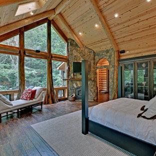 Cette image montre une chambre chalet avec un sol en bois foncé, un manteau de cheminée en pierre et une cheminée d'angle.