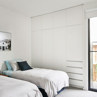 Inspiration for a beach style bedroom in Geelong with white walls, carpet and grey floor.