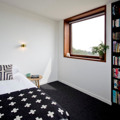 Mid-sized trendy master carpeted and black floor bedroom photo in Melbourne with white walls