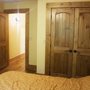 Diseño de habitación de invitados rústica, grande, con paredes beige, suelo de madera oscura y suelo multicolor