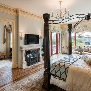 Inspiration for a large eclectic master medium tone wood floor bedroom remodel in Orlando with blue walls, a two-sided fireplace and a stone fireplace