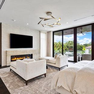 Modelo de dormitorio principal, minimalista, grande, con paredes beige, suelo de madera en tonos medios, chimenea lineal, marco de chimenea de piedra y suelo marrón
