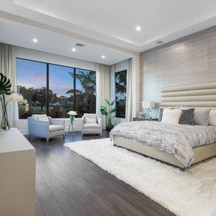 Modernes Schlafzimmer mit grauer Wandfarbe, dunklem Holzboden, braunem Boden, Tapetenwänden und eingelassener Decke in Miami