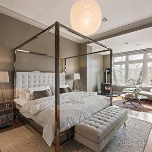 Modelo de dormitorio principal, clásico renovado, con paredes grises, suelo de madera en tonos medios, estufa de leña y suelo marrón