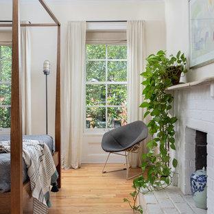 На фото: спальня в стиле современная классика с белыми стенами, паркетным полом среднего тона, стандартным камином, фасадом камина из кирпича и коричневым полом с