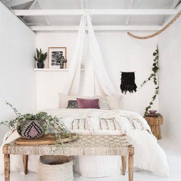 Bohemian beach style bedroom featuring handmade wall hangings