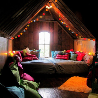 Modelo de dormitorio ecléctico con suelo de madera oscura