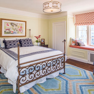 This is an example of a mid-sized traditional guest bedroom in San Francisco with yellow walls, dark hardwood floors, no fireplace and brown floor.