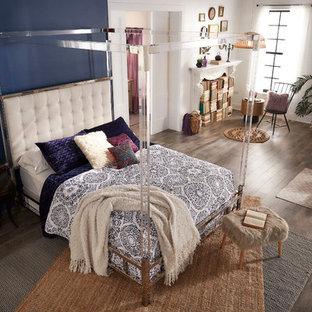 Diseño de dormitorio principal, bohemio, de tamaño medio, con paredes azules, suelo de madera clara, chimenea tradicional, marco de chimenea de yeso y suelo marrón