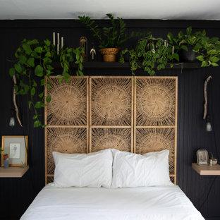 Kleines Skandinavisches Hauptschlafzimmer ohne Kamin mit schwarzer Wandfarbe, Laminat, beigem Boden und Wandpaneelen in Grand Rapids
