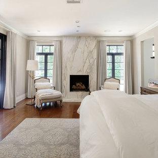 Großes Mediterranes Hauptschlafzimmer mit beiger Wandfarbe, braunem Holzboden, Gaskamin und gefliester Kaminumrandung in Orange County