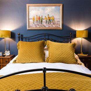Ejemplo de dormitorio principal, tradicional, grande, sin chimenea, con paredes azules, suelo de madera oscura, marco de chimenea de piedra y suelo marrón