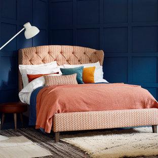 Imagen de dormitorio principal, clásico, grande, sin chimenea, con paredes azules y suelo de cemento