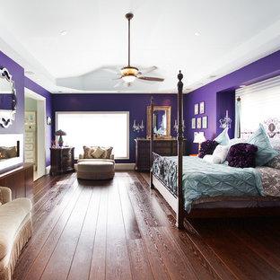 Imagen de dormitorio principal, contemporáneo, de tamaño medio, con paredes púrpuras, suelo de madera oscura, chimenea de doble cara, marco de chimenea de metal y suelo marrón