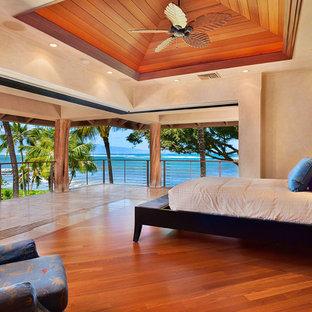 Diseño de dormitorio principal, tropical, grande, sin chimenea, con paredes beige, suelo de madera en tonos medios y suelo marrón