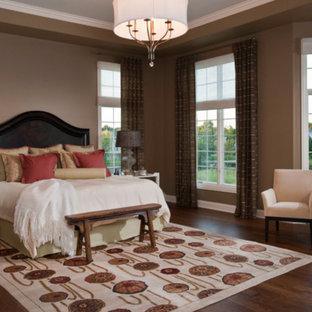 Imagen de dormitorio principal, tradicional, grande, sin chimenea, con paredes beige, suelo de madera oscura y suelo rojo