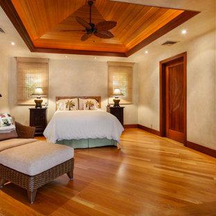Imagen de dormitorio principal, tropical, grande, sin chimenea, con paredes beige, suelo de madera oscura y suelo rojo