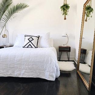 Esempio di una camera matrimoniale tropicale di medie dimensioni con nessun camino, pavimento marrone, pareti bianche e parquet scuro