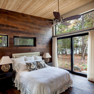 Inspiration for a large country master bedroom in Other with beige walls, dark hardwood floors, brown floor and a hanging fireplace.