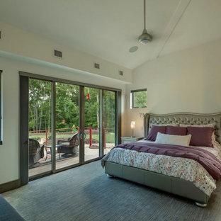 Diseño de dormitorio principal, actual, con paredes blancas, moqueta, chimenea de doble cara, marco de chimenea de baldosas y/o azulejos y suelo gris