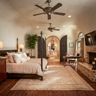 Photo of a mid-sized mediterranean master bedroom in Houston with beige walls, a standard fireplace, a brick fireplace surround, dark hardwood floors and brown floor.